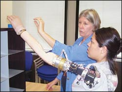 Kathy Stubblefield, OTR/L, watches patient Claudia Mitchell as she conducts functional testing with the six-motor neural-controlled prosthesis. Photograph courtesy of the Rehabilitation Institute of Chicago.